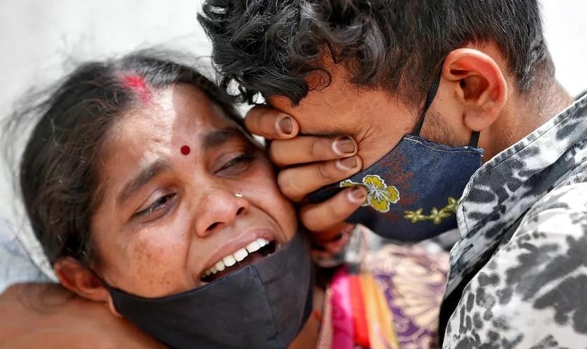 Mulher chora com seu filho depois que seu marido morreu devido à Covid-19 fora de um necrotério em Ahmedabad, na Índia. (Foto: Amit Dave / Reuters)