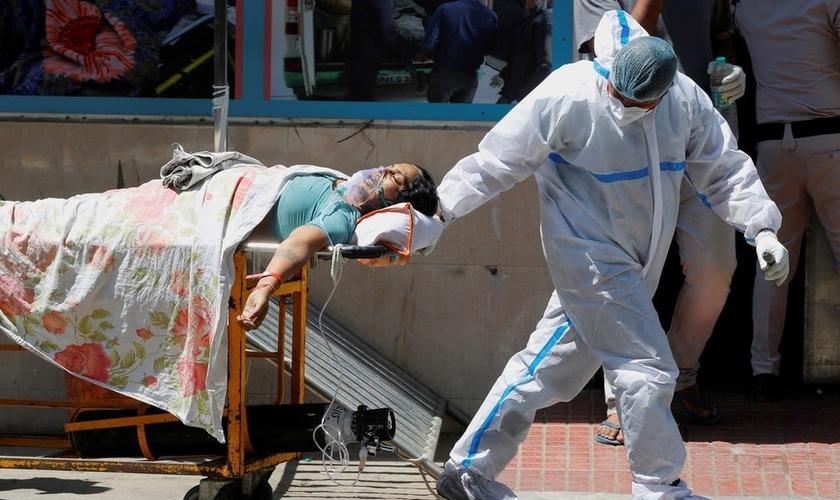 Profissional de saúde leva paciente com Covid-19 em hospital de Nova Delhi, na Índia, neste sábado (24). (Foto: Adnan Abidi/Reuters).