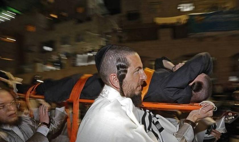 Vítimas são socorridas após arquibancada desabar em sinagoga próxima a Jerusalém, na noite de 16 de maio de 2021. (Foto: Gil Cohen-Magen / AFP)