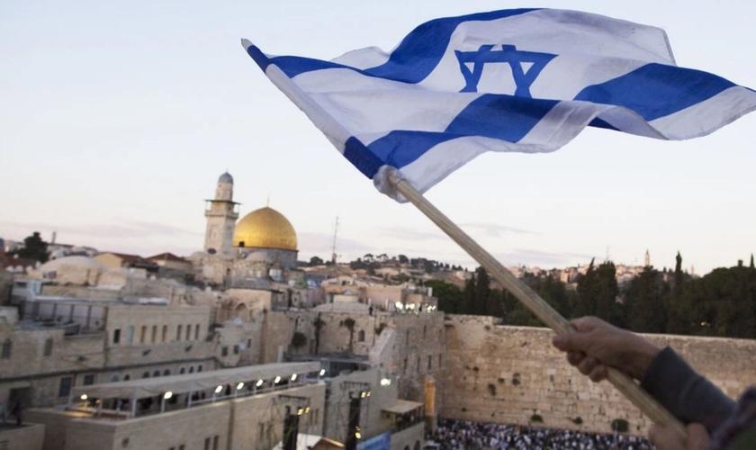 Bandeira israelense sendo hasteada perto do Muro das Lamentações no Dia de Jerusalém, em 13 de maio. (Foto: Lior Mizrahi/Getty Images)