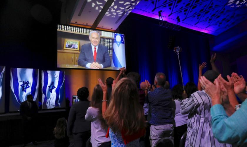 O Primeiro Ministro de Israel Netanyahu discursa em uma cúpula dos Cristãos Unidos por Israel em Washington, em julho de 2018. (Foto: Twitter/Reprodução).