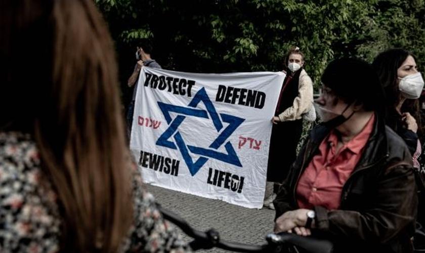 Participantes de uma vigília contra o antissemitismo se reúnem em frente à sinagoga em Kreuzberg, Berlim, no domingo. (Foto: Filip Singer / EPA)