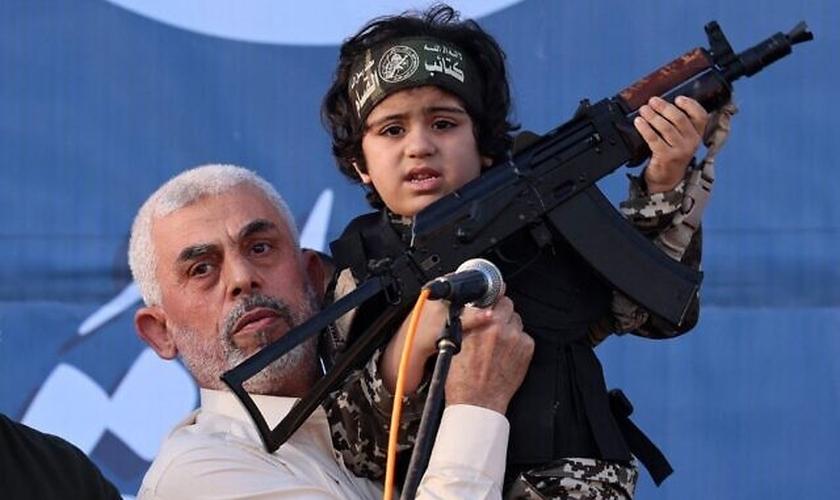 Líder do Hamas, Yahya Sinwar, segura o filho de um membro que foi morto no confronto com Israel. (Foto: Emmanuel Dunand/AFP)