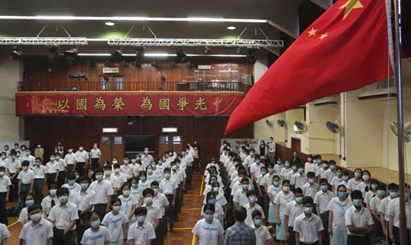 Alunos participam de uma cerimônia de hasteamento da bandeira, no Dia da Educação para a Segurança Nacional, numa escola em Hong Kong, 15 de abril de 2021. (Foto: AP Photo/Kin Cheung)
