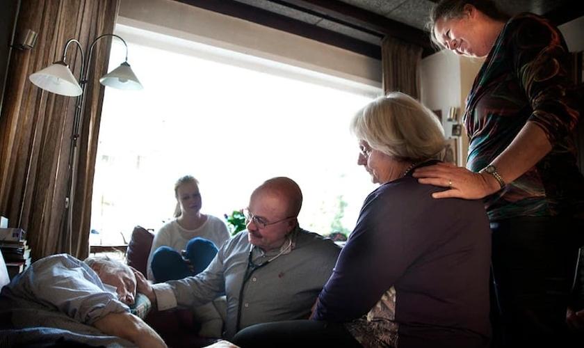 A família e o médico Sjef Boesten (com estetoscópio) se reúnem enquanto a vida de Siep Pietersma se esvai (Foto: Mona van den Berg)