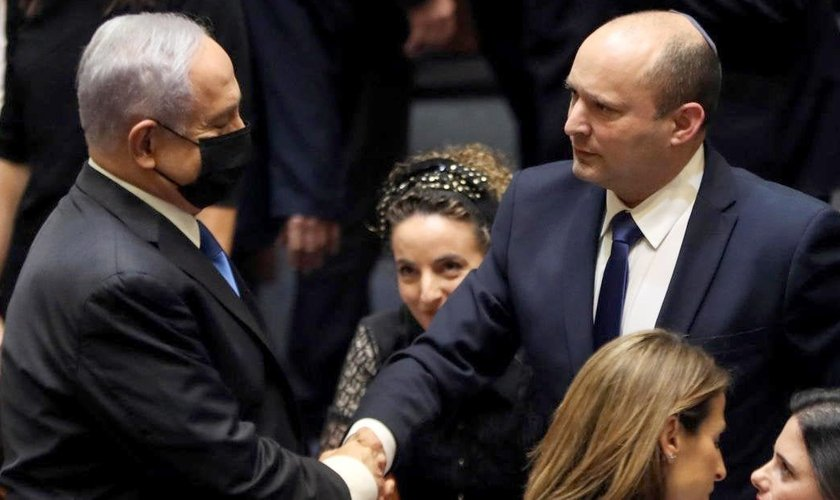 Benjamin Netanyahu e Naftali Bennett apertam as mãos após votação no Knesset. (Foto: Reuters/Ronen Zvulun)
