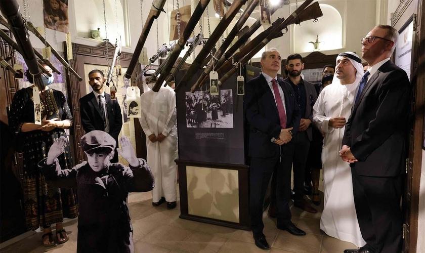 Embaixador de Israel nos Emirados Árabes Unidos, Eitan Na'eh (3º à direita), Ahmed Al Mansuri, fundador do Crossroads of Civilization Museum (2º à direita), e embaixador alemão nos Emirados Árabes Unidos, Peter Fischer (à direita), na exposição. (Foto: Re