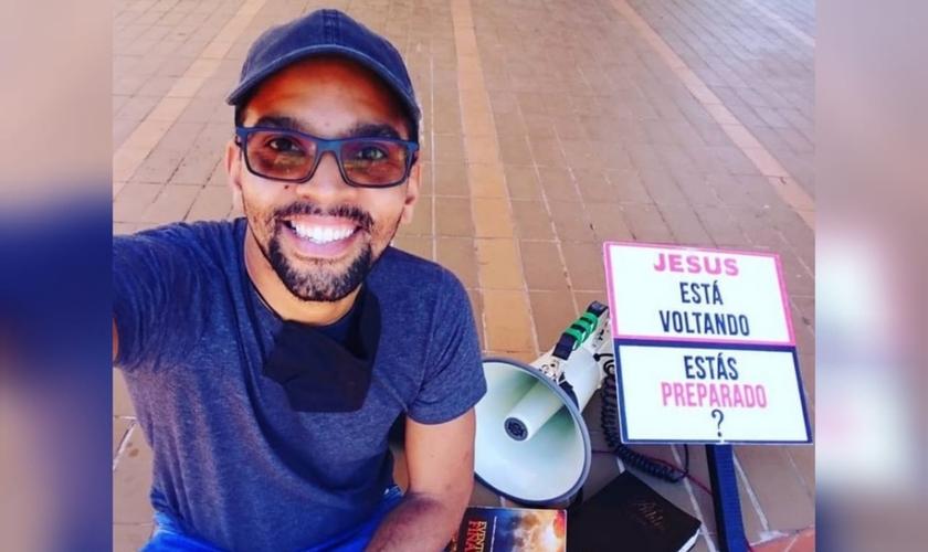 """Wanderson Campos evangeliza com um megafone e uma placa """"Jesus está voltando"""" nas ruas de Cuiabá (MT). (Foto: Arquivo pessoal)."""
