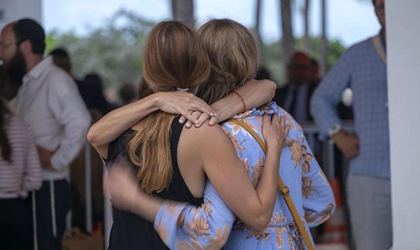 Depois de ouvir a notícia do colapso do prédio do condomínio, os moradores se agarram uns aos outros em Miami, EUA. (Foto: Billy Graham Association).