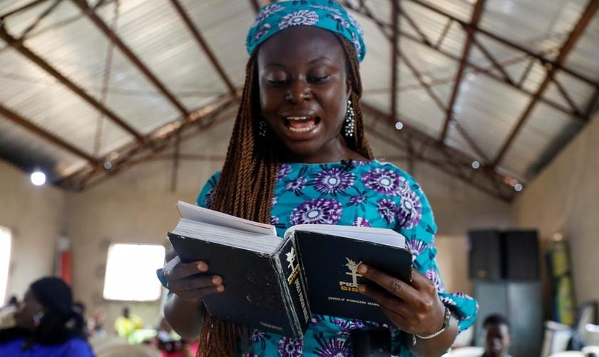 Mulher e a Bíblia Pidgin durante culto na Igreja do Cidadão Celestial em Lagos, Nigéria. (Foto: Reuters / Temilade Adelaja)