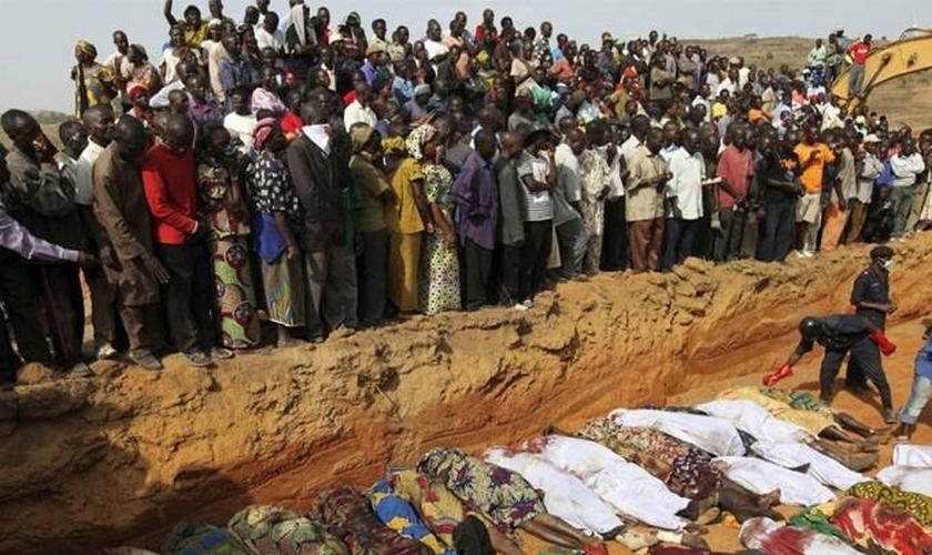 Aldeões observando corpos de vítimas de violência étnica entre fazendeiros de Berom e pastores Fulani, na vila de Dogo Nahawa, na Nigéria, em 2010. (Foto: Reuters).