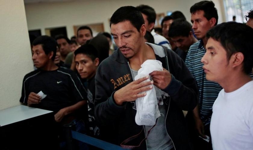 Imigrantes ilegais aguardam enquanto recebem seus pertences e processam sua volta ao aeroporte de La Aurora (Guatemala), de onde saíram.