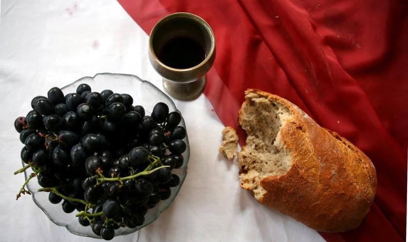 Mesa posta para Páscoa com o cálice, pão e uvas