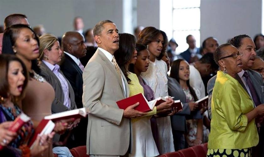 Na imagem, Barack Obama aparece junto à sua família, participando de um culto em meio a outros fiéis.