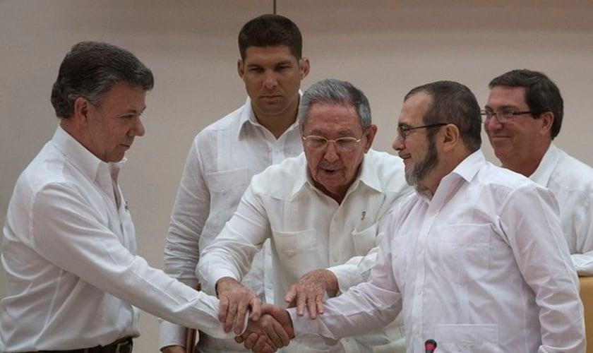 Presidente da Colômbia Juan Manuel Santos e o líder das FARC Timoleón Jiménez cumprem ato simbólico para acordo de paz, na frente do presidente cubano Raúl Castro (Foto: AP Photo / Desmond Boylan)