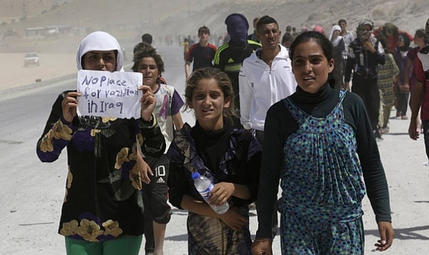 Mulheres e homens da etnia Yazidi em fuga da opressão imposta pelo Estado Islâmico na cidade de Sinjar. (Foto: Reuters / YOUSSEF BOUDLA)