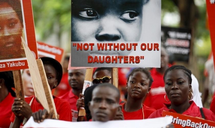 """Familiares e amigos participam de manifestação, clamando pelo resgate das meninas sequestradas pelo Boko Haram em 2014, segurando placas como esta, que diz """"Não sem nossas filhas""""e com o lema """"Tragam nossas garotas de volta"""" (Foto: Reuters)"""