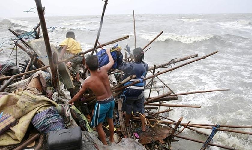 Uma família que vive na baía de Manila tenta achar pertences que possam ser recuperados, após a sua casa ter sido destruída por fortes ventos trazidos pelo tufão Koppu neste domingo, 18/10. (Foto: Romeo Ranoco/Reuters)