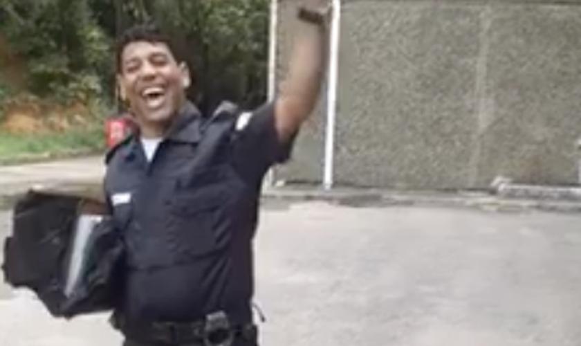 """Usando a farda policial, o homem canta trechos do """"Corinhos de Fogo"""", de Andréa Fontes. (Foto: Reprodução/Facebook)"""