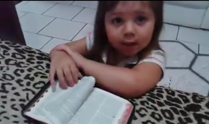 Ajoelhada em frente a uma cama, com os braços apoiados sobre uma Bíblia, a menina inicia suas preces. (Foto: Reprodução)