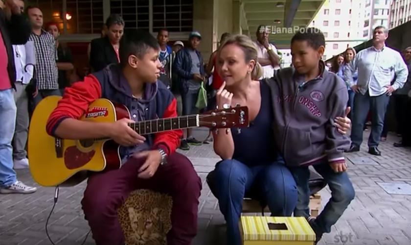 Pelas ruas, Thiago e Miguel cantam músicas gospel para expressar sua fé e conseguir alguns trocados. (Foto: Reprodução/SBT)