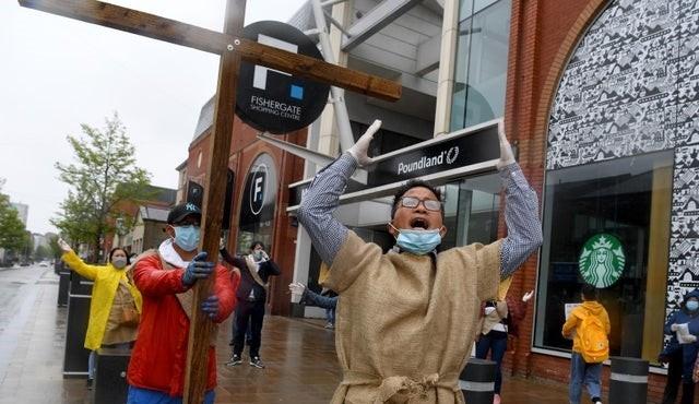 Cristãos chineses oram e cantam em rua de cidade do Reino Unido