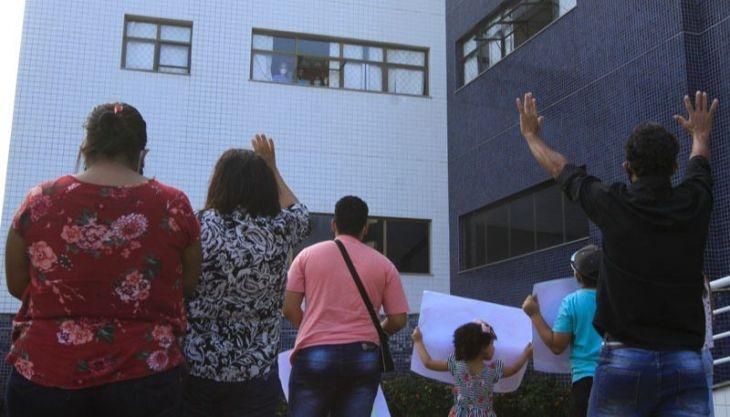 Família canta louvores no pátio de hospital e ora por jovem internado há 30 dias