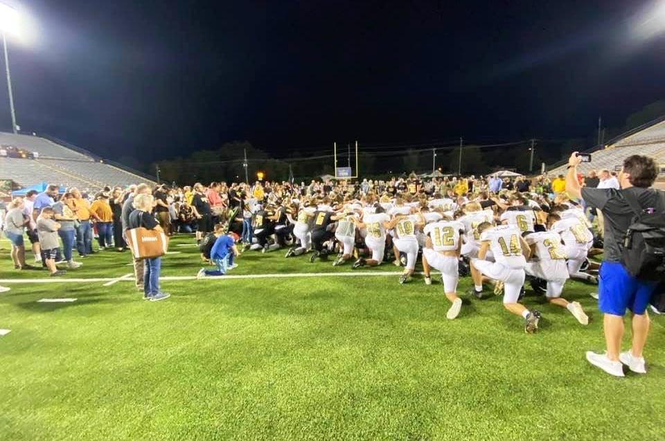 Equipe de futebol desafia proibição e leva arquibancada à oração após jogo