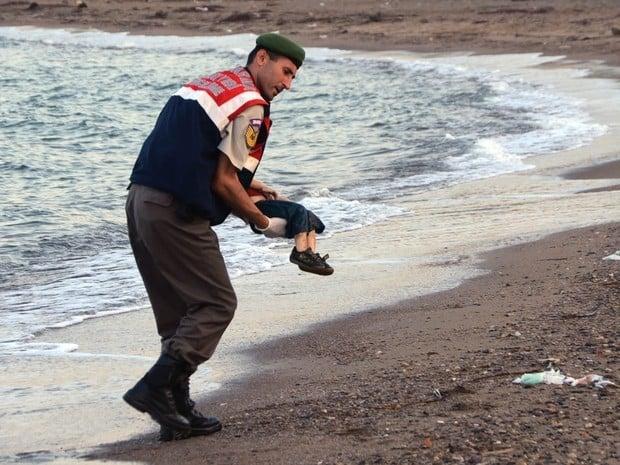 Policial carrega o corpo do garoto sírio