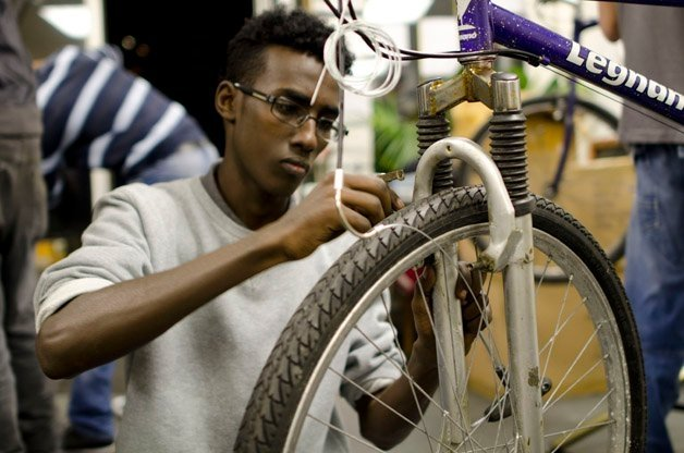 ONG criada por refugiados instalados em Londres ensina recém-chegados a trabalhar consertando bicicletas